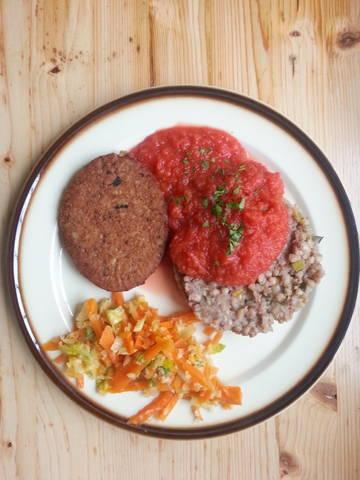 Trigo sarraceno con puerros y tomato, acompañado por una hamburguesa vegetal y picles